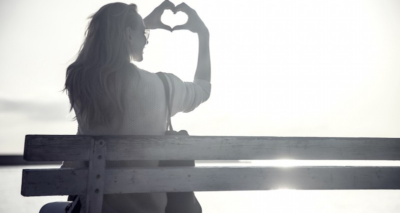 Young woman looking at amazing sunrise, showing heart symbol