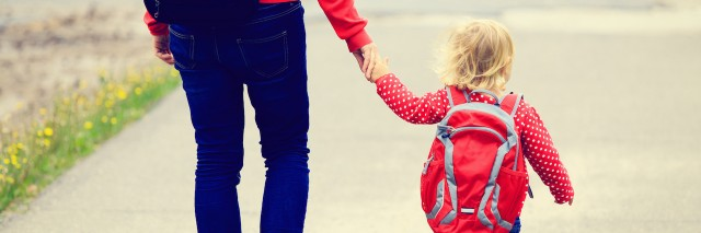 Mother holding hand of little daughter with backpack going to school