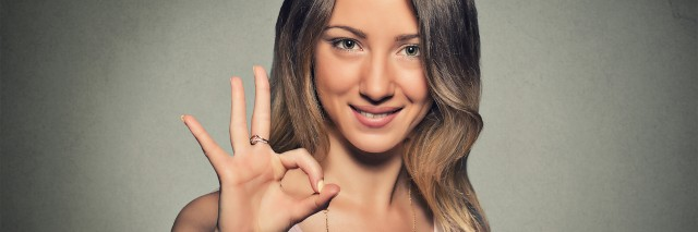 Beautiful happy young woman showing Ok sign isolated on gray wall background.