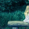 child sitting and waiting on wooden bench