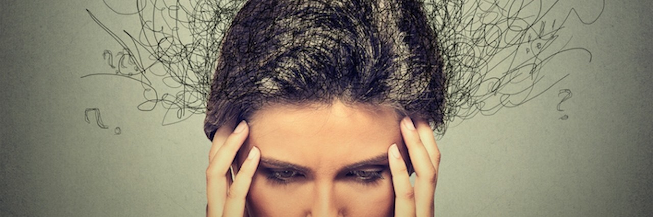 woman stressed holding her head