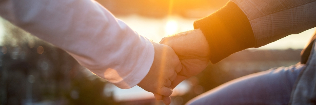 Unrecognizable romantic couple holding hands at sunset.