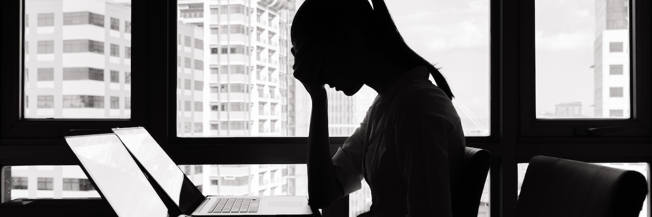 A photographic image of a stressed businesswoman sitting at a desk. The woman is seated in front of a window with a bright light source, rendering her image as a shadowed silhouette with indiscernible features. She is leaning forward with her elbows against the top of the desk and her hands clasped against her face, with her head slightly bent forward.