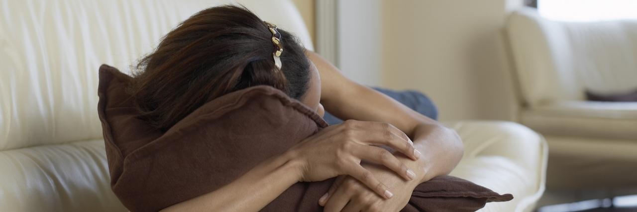 Woman sleeping on sofa with arm around pillow