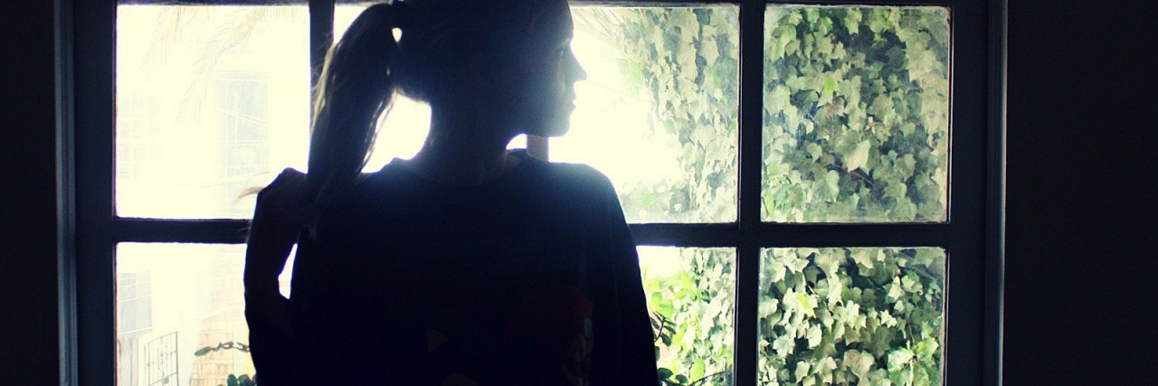 lonely woman standing by window