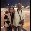 woman standing with saxophone player on the street