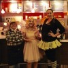 three women wearing Halloween costumes at a restaurant