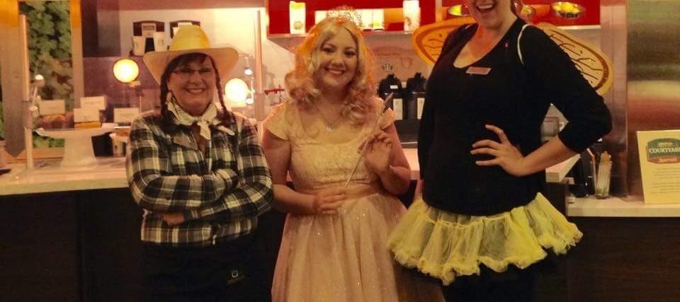 three women wearing Halloween costumes at a restaurant