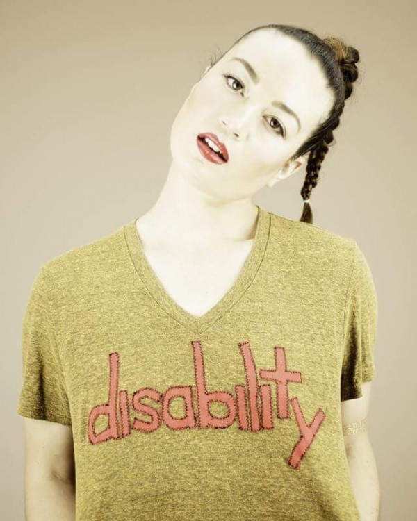 """Charis wearing a t-shirt with hand-stitched lettering that says """"disability."""""""