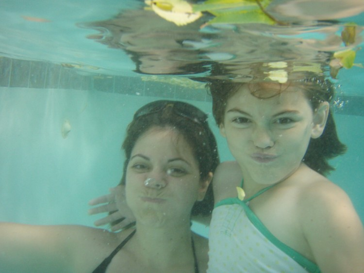 woman and little girl underwater in pool