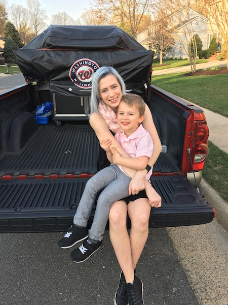 Woman sitting on back of a truck with her child.