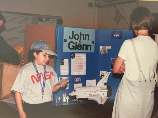 girl giving presentation about john glenn in school