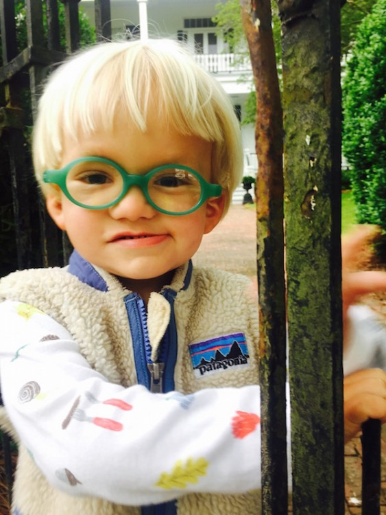 young boy wearing green glasses