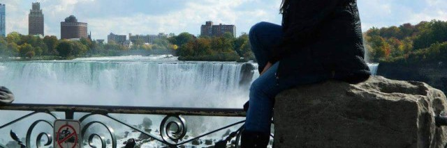 woman sitting on a rock with a river and skyline int he background