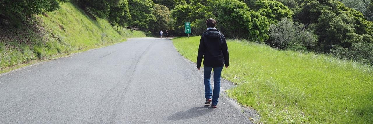 Karina walking down a road.