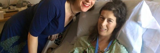 woman lying in hospital bed with her sister standing next to her