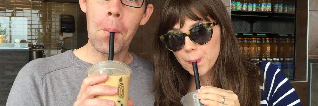 man and woman sipping cups of tea with straws
