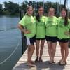 four teen girls wearing green shirts standing on a dock