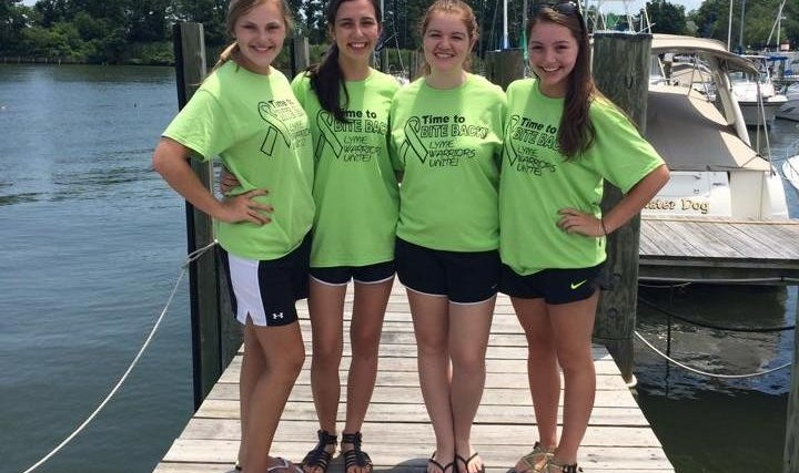 four teen girls wearing green shirts standing on a dock