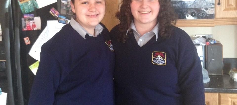 two teenage girls wearing school uniforms standing in kitchen