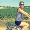 woman riding bike in field