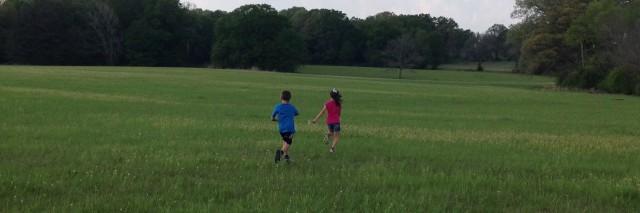 boy and girl running away on grass