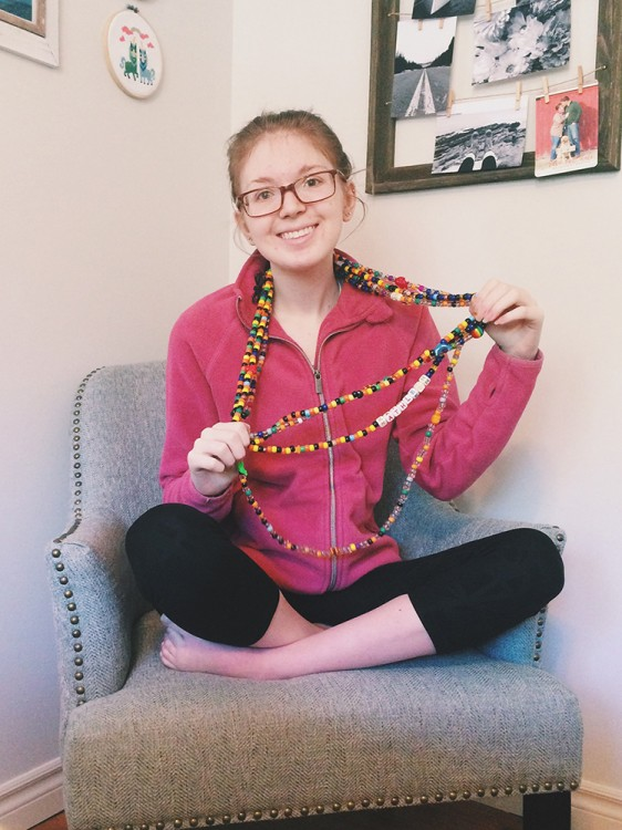 Kathleen sitting in a chair smiling, showing off her beaded necklaces