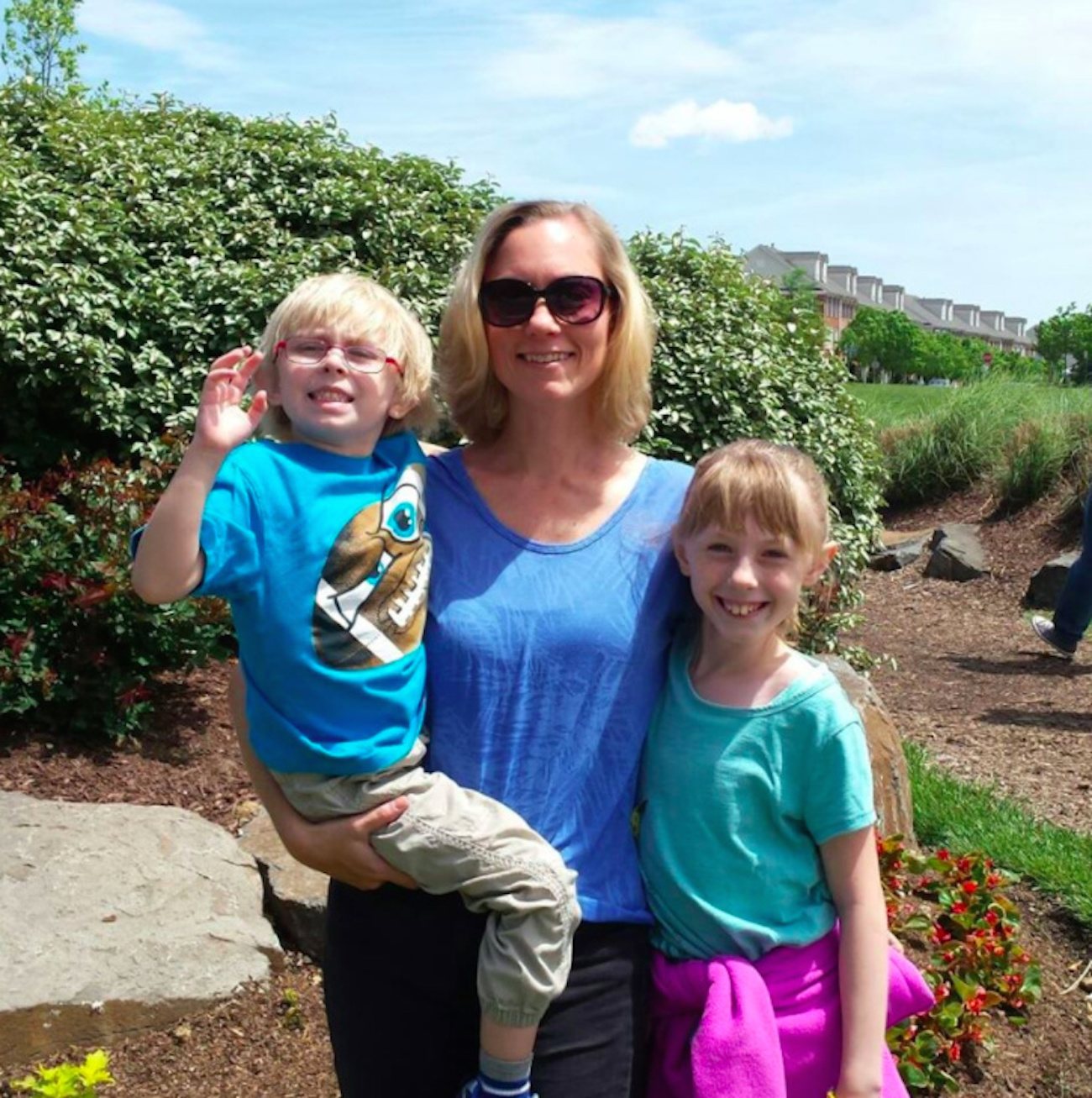 mom holding son and standing next to daughter near garden outdoors