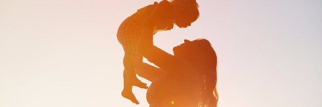 mother holds child in front of sunset