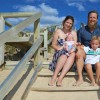 a family including mom dad baby girl and young son sitting on a staircase outdoors by a beach