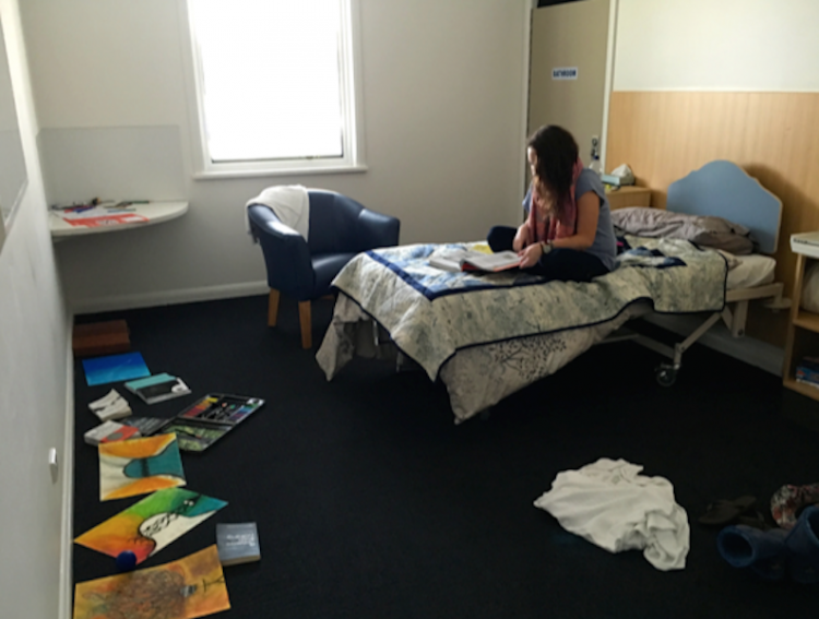 a woman sitting on her bed at a psychiatric hospital