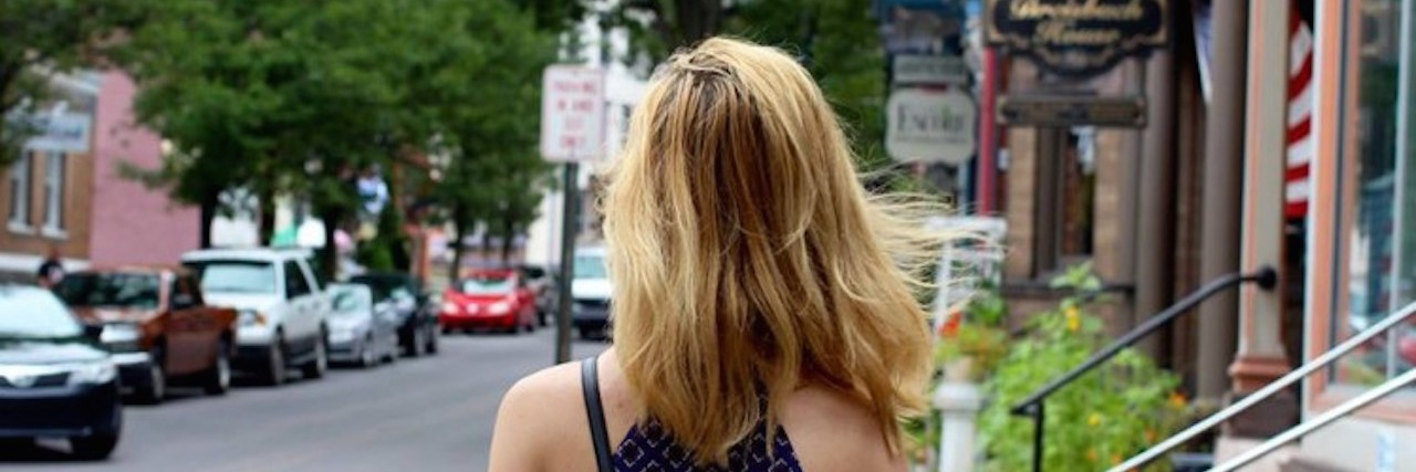 The back of a woman's head standing on a side walk