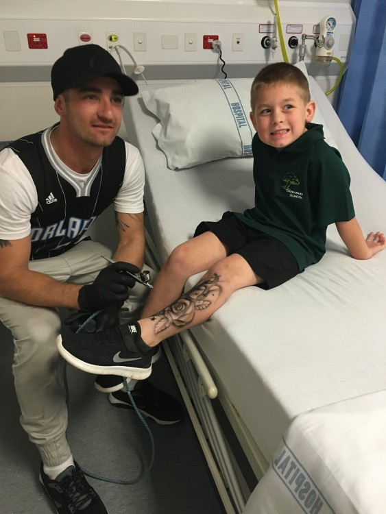 Lloyd tattooing a young boy sitting on a hospital bed