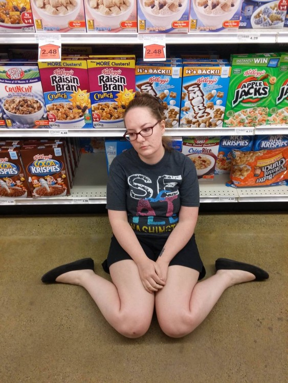 girl sitting on floor of grocery store in cereal aisle