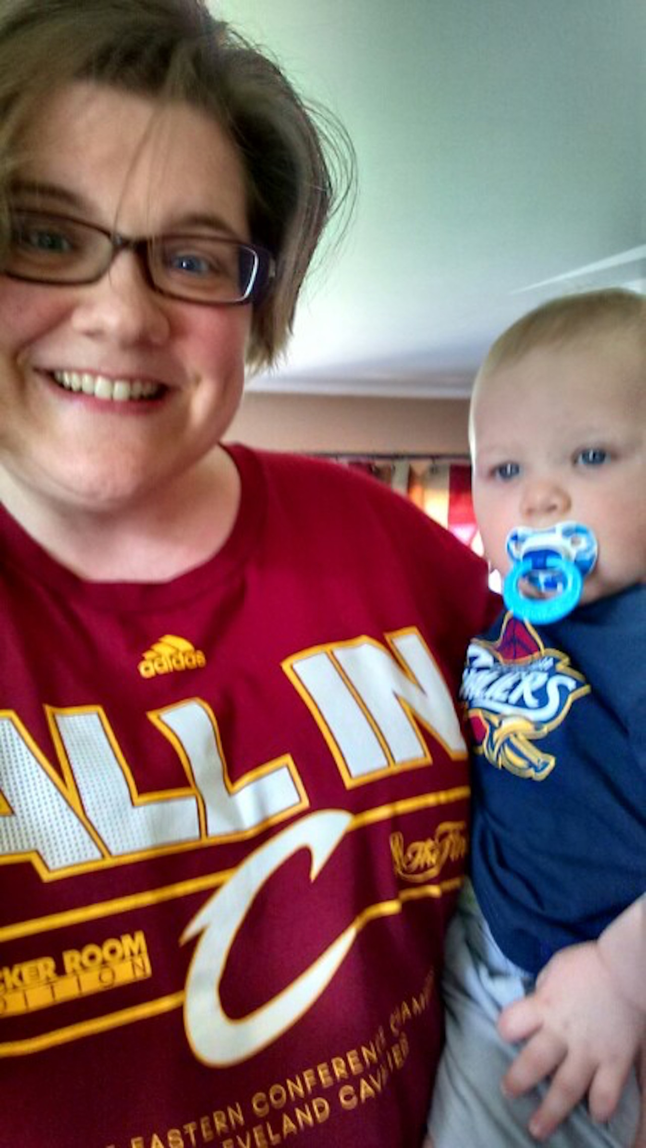 mom in cavs shirt holding baby in cavs shirt