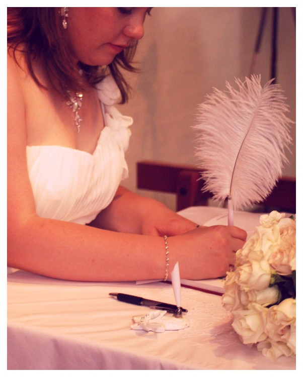 bride writing on a table using a feather pen
