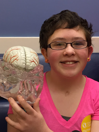 Amelia smiling holding a model of a brain