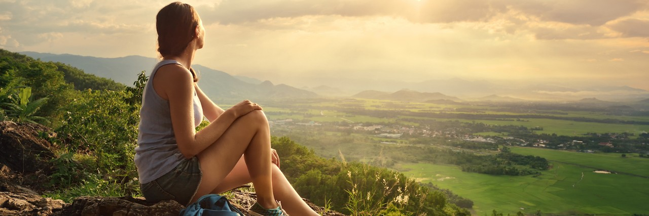 Young woman sitting on the edge of a cliff looking at the valley and mountains