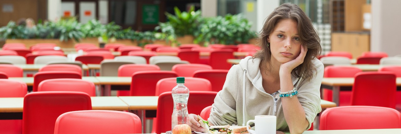 Frustrated woman sitting at lunch table