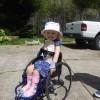 Heidi in her wheelchair smiling
