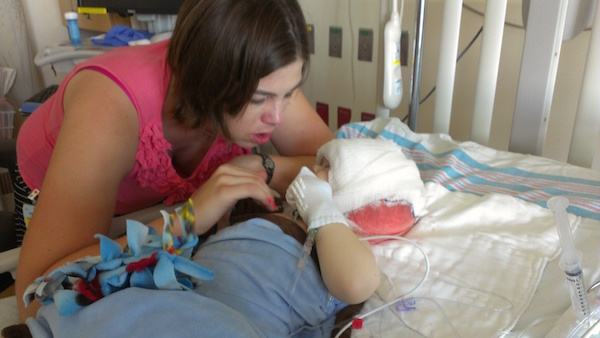 Kathy looking at her son, who lays in a hospital bed. His head is covered with gauze.