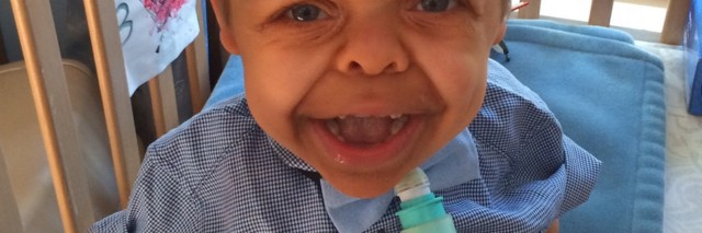 boy with dwarfism smiling in his crib