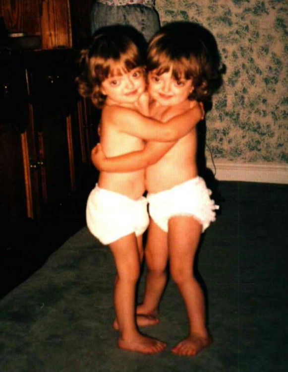 Ariel and her sister in diapers hugging