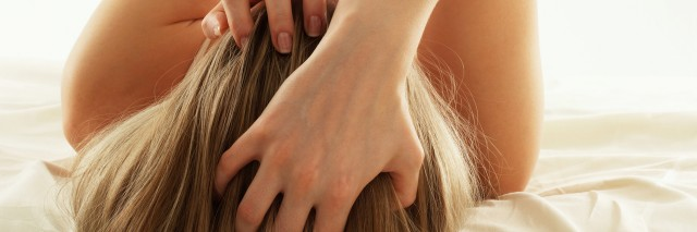 Rear view image of woman with blonde hair runs her fingers through her hair