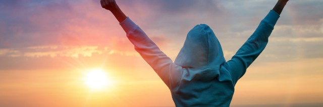 Woman stands with her arms stretched out in victory in front of a setting sun