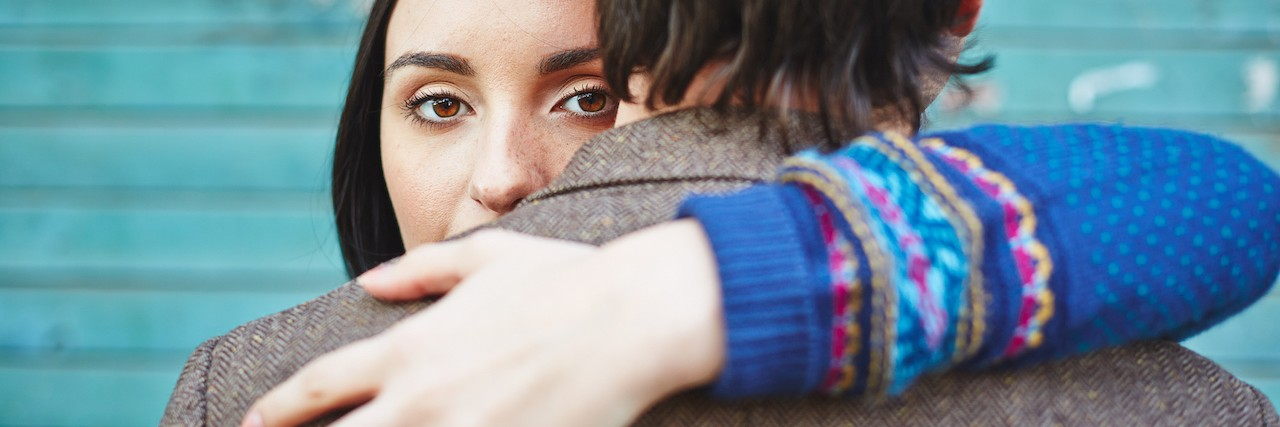Woman looking at camera while embracing man who faces opposite direction