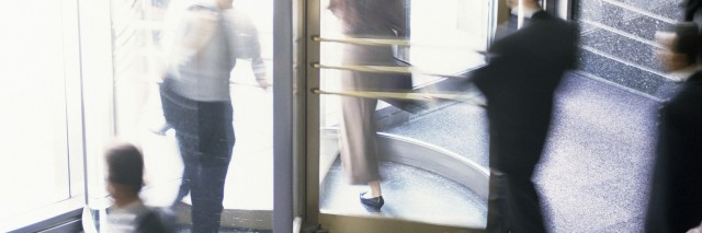 People walking through a revolving door