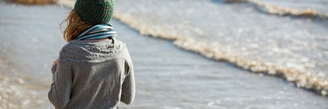 girl in knit hat and sweater, walking on the coast