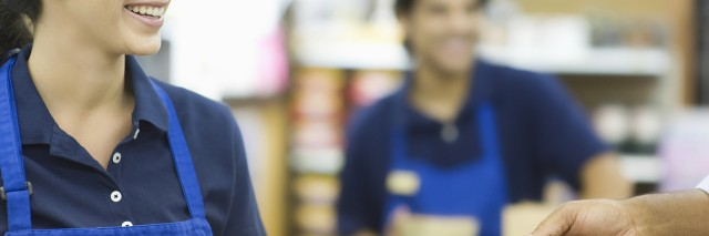 Two service industry workers in aprons, one handing a credit card to a customer