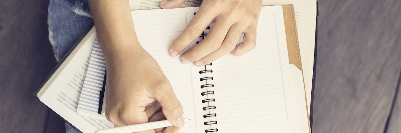 Girl writes letter in notebook
